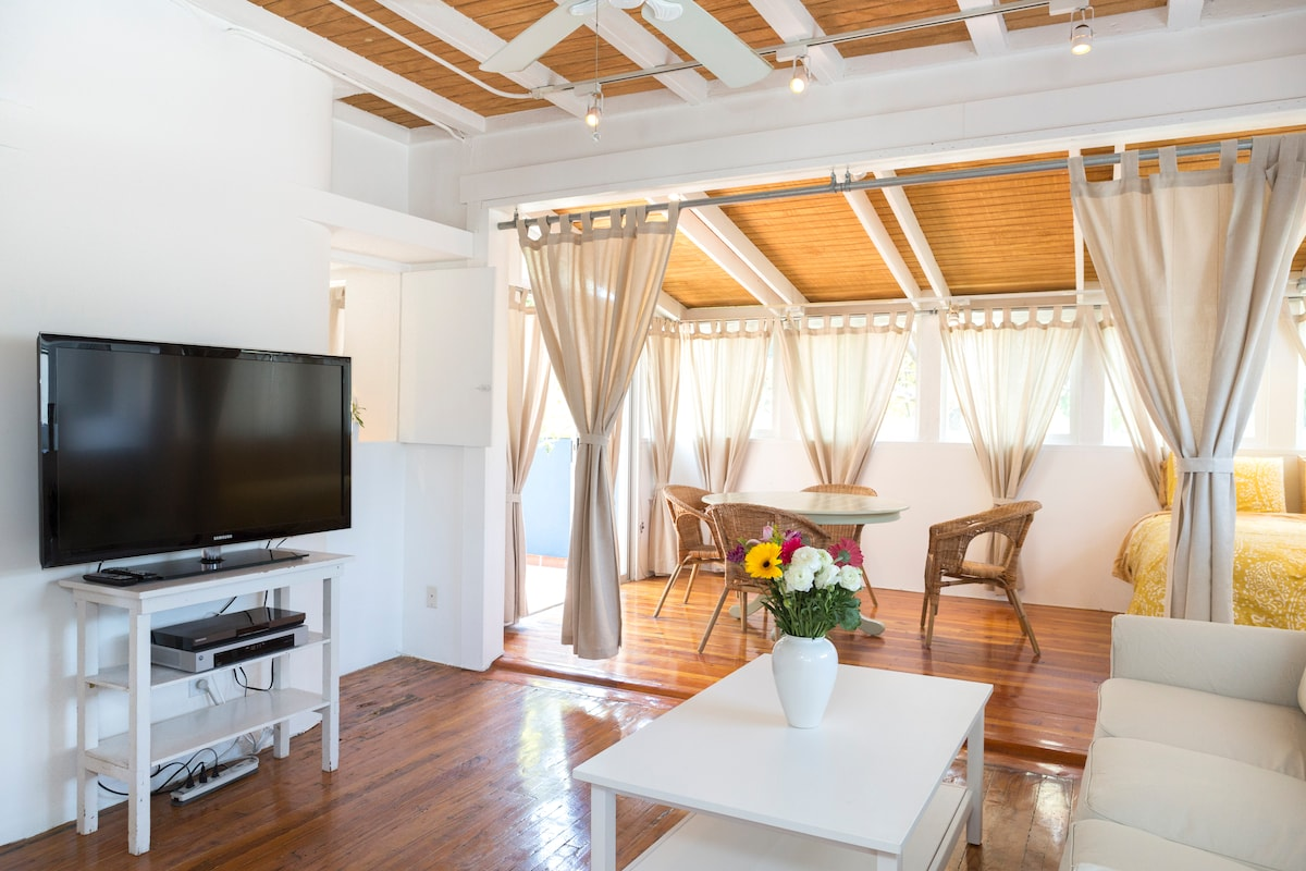 Living room with TV, sofa, dining table. Curtains can be closed to section off second sleeping area.