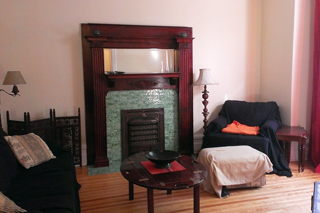 Living room with comfy chairs and a beautiful old electric fireplace & mantlepiece.