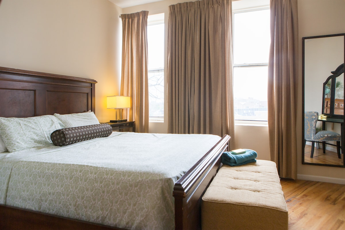 Master bdrm equipped with a king size bed.