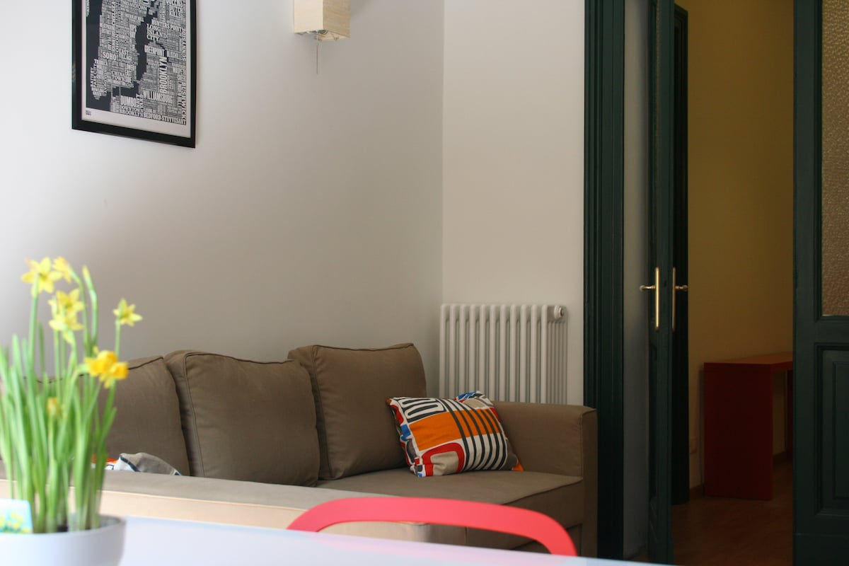A view of the sofa bed in the dining room, and the door to the entrance hall