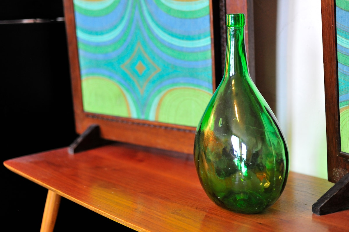 An antique Portuguese glass bottle, with vintage 1969 speakers behind it...