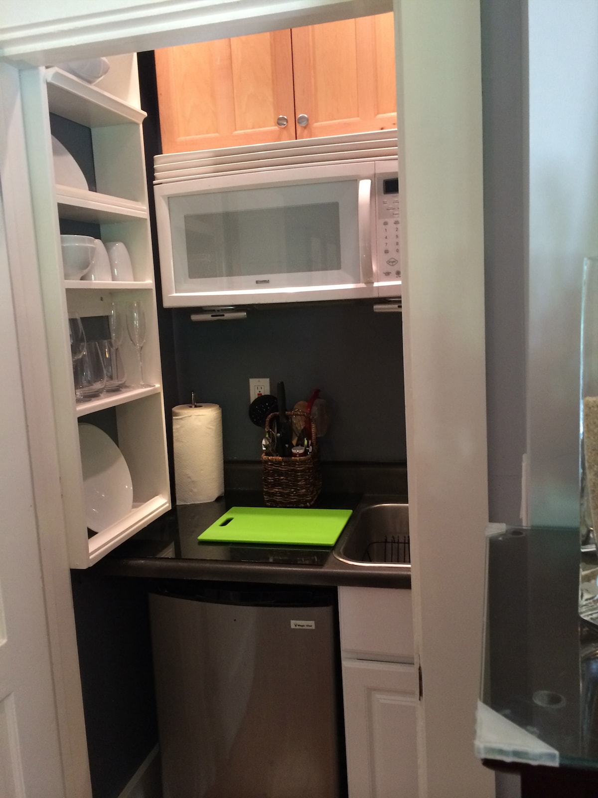 Small Kitchenette with Microwave, Kourig Coffee maker, sink, fridge, induction plate, toaster and all plates and cups etc.