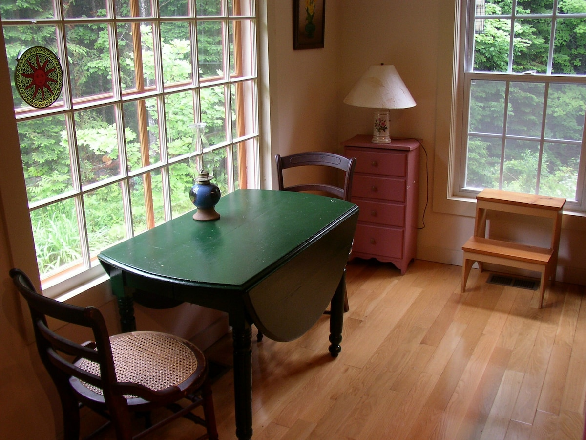 Cozy table by the window to watch birds and stream