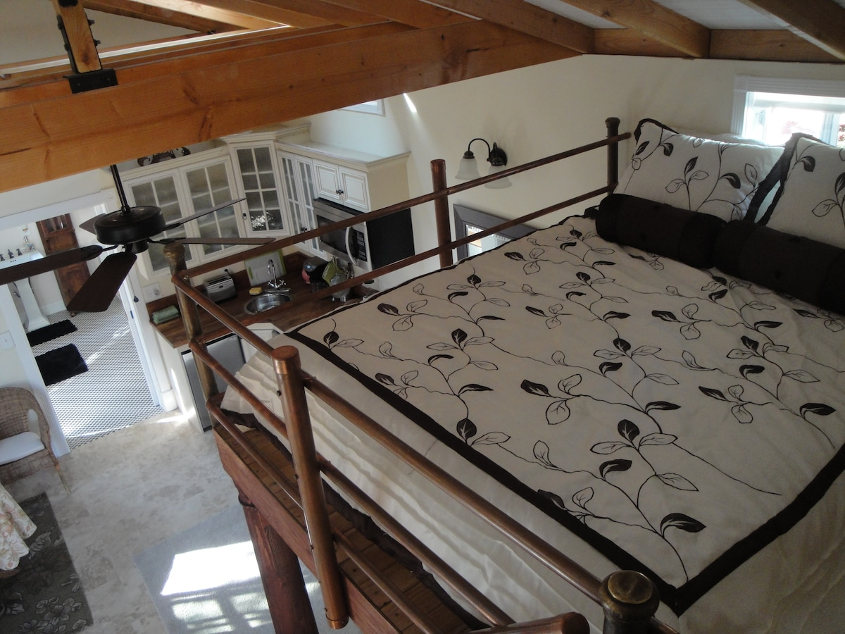 Loft queen size bed and overview from top of stairs toward kitchen and bathroom