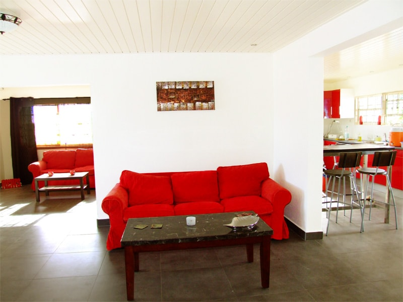 Living room with comfortable sofa and view to the TV-area (left) and kitchen (right)