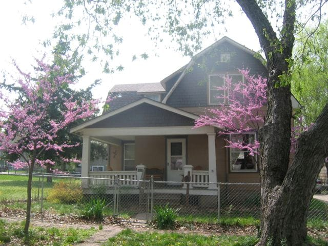 VIew of House looking west. Redbuds in bloom in Spring. Two adirondack recliners and wrought iron bench.