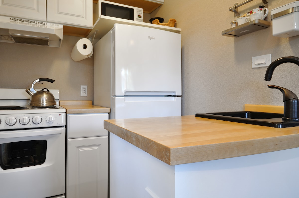 Small kitchenette; stove-top, oven, freezer w/ ice maker, refrigerator, dishes, glasses, supplies.