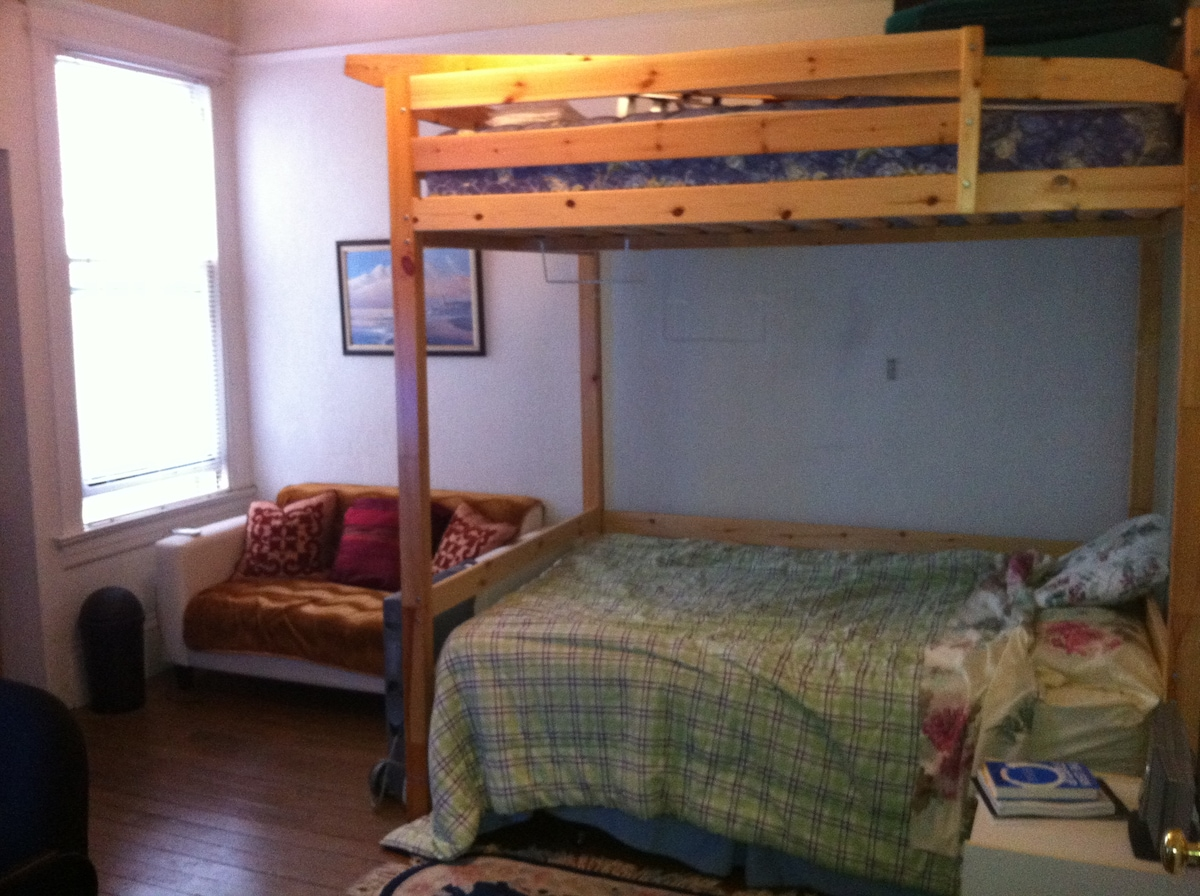 Two full-size beds. One wall mounted loft bed with another bed slide under neath. Extra high ceiling not shown in the picture. Upper bed not being used in this picture.  Ladder laid on top with other stored items.