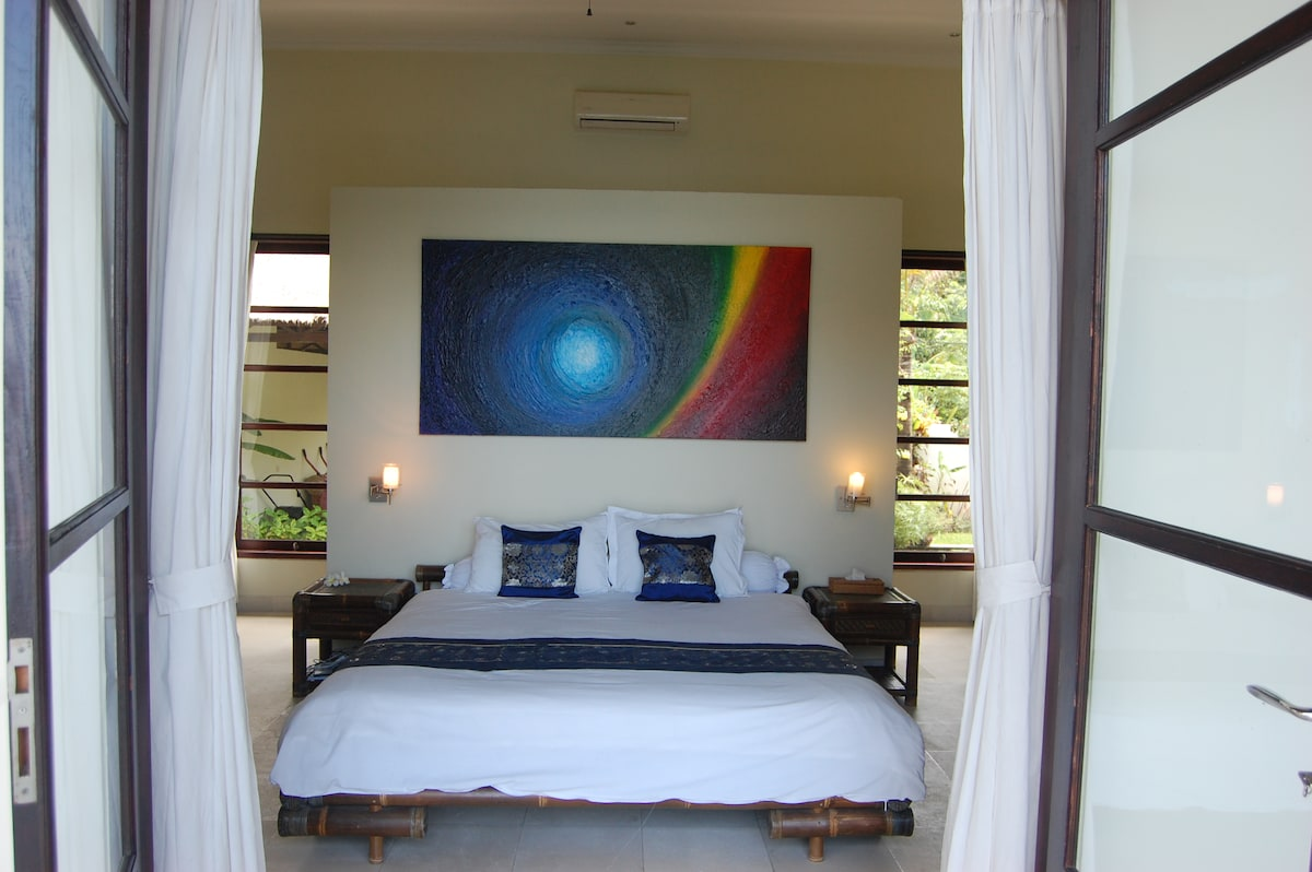 Bedroom 1 - artwork by Valerie - windows overlook swimming pool and sea - back windows to front garden