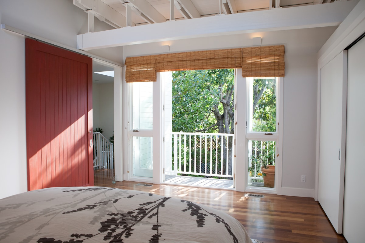Upstairs Master Bedroom: French doors leading to deck overlooking front yard. The sliding red barn door leads to Master Bathroom and downstairs