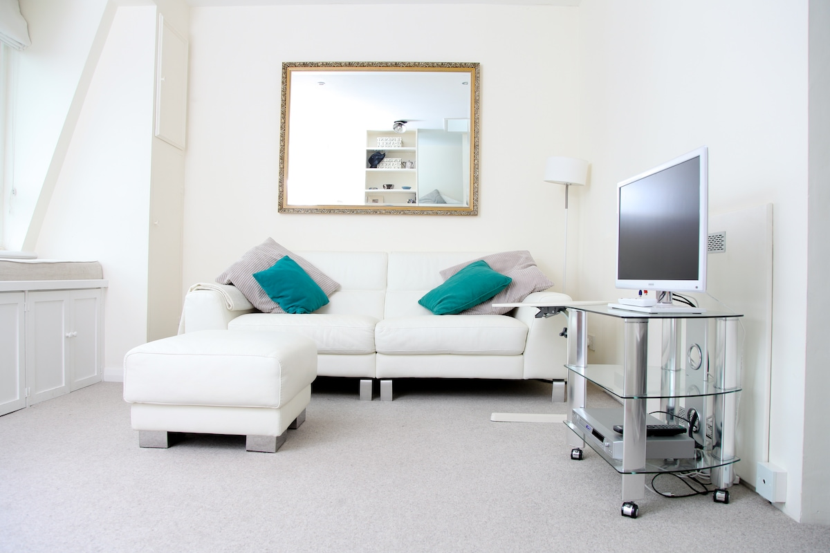 White leather sofa and stool with simple laptop table behind the TV and DVD player