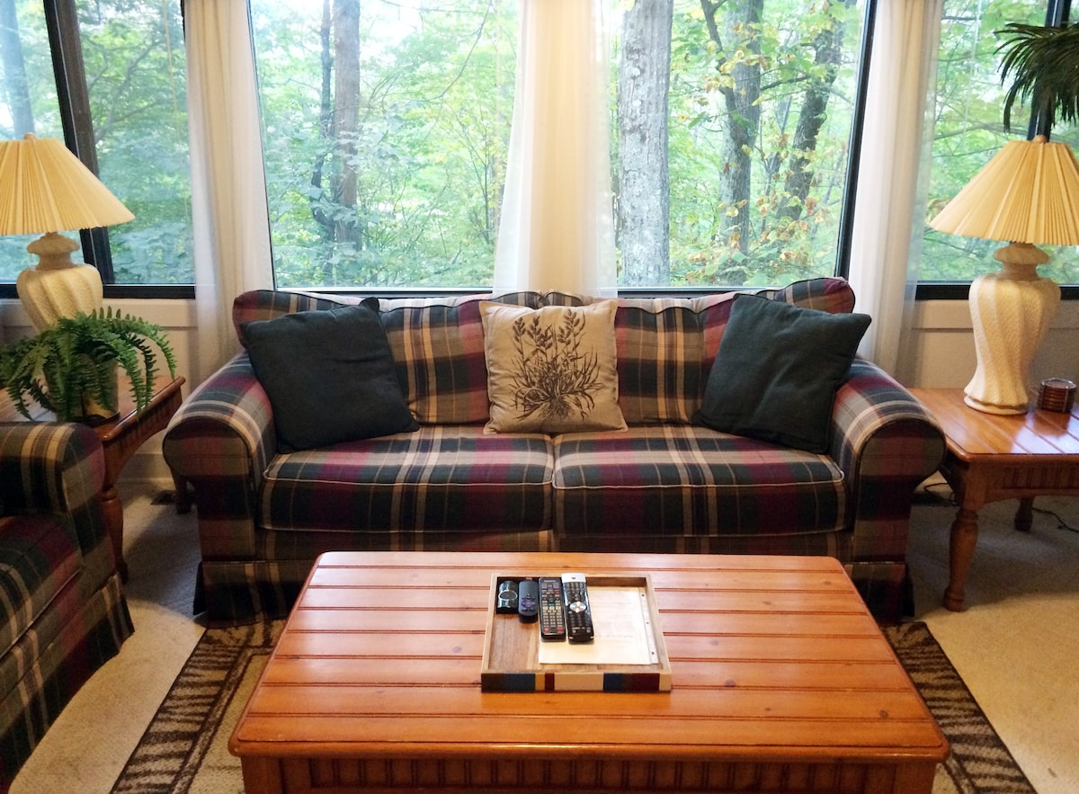 A spacious living room with couch, love seat, and TV!