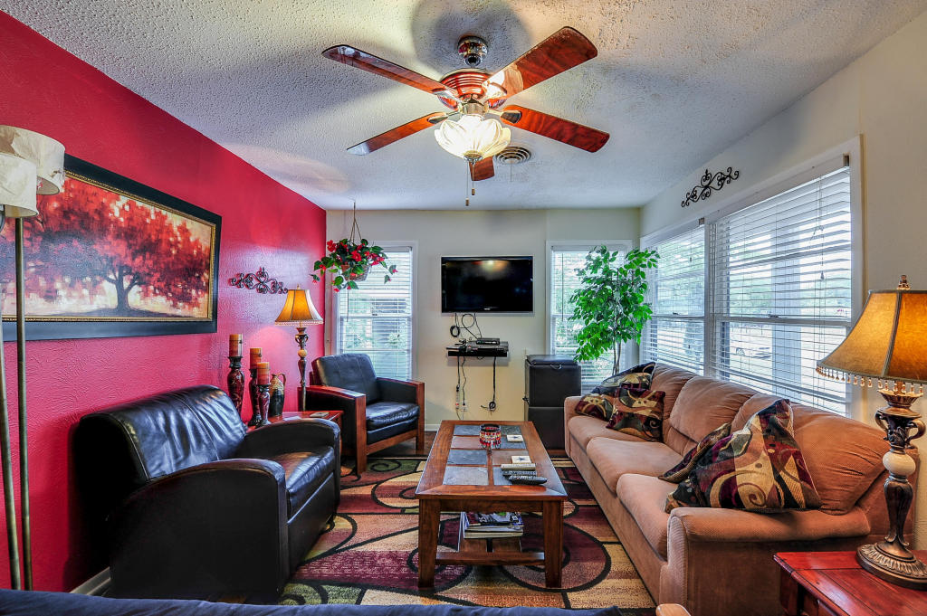 """Bright living area with plenty of seating for everyone.  Extra ottomans can be used for seats, trays or storage.  40"""" Television has cable with DVR."""