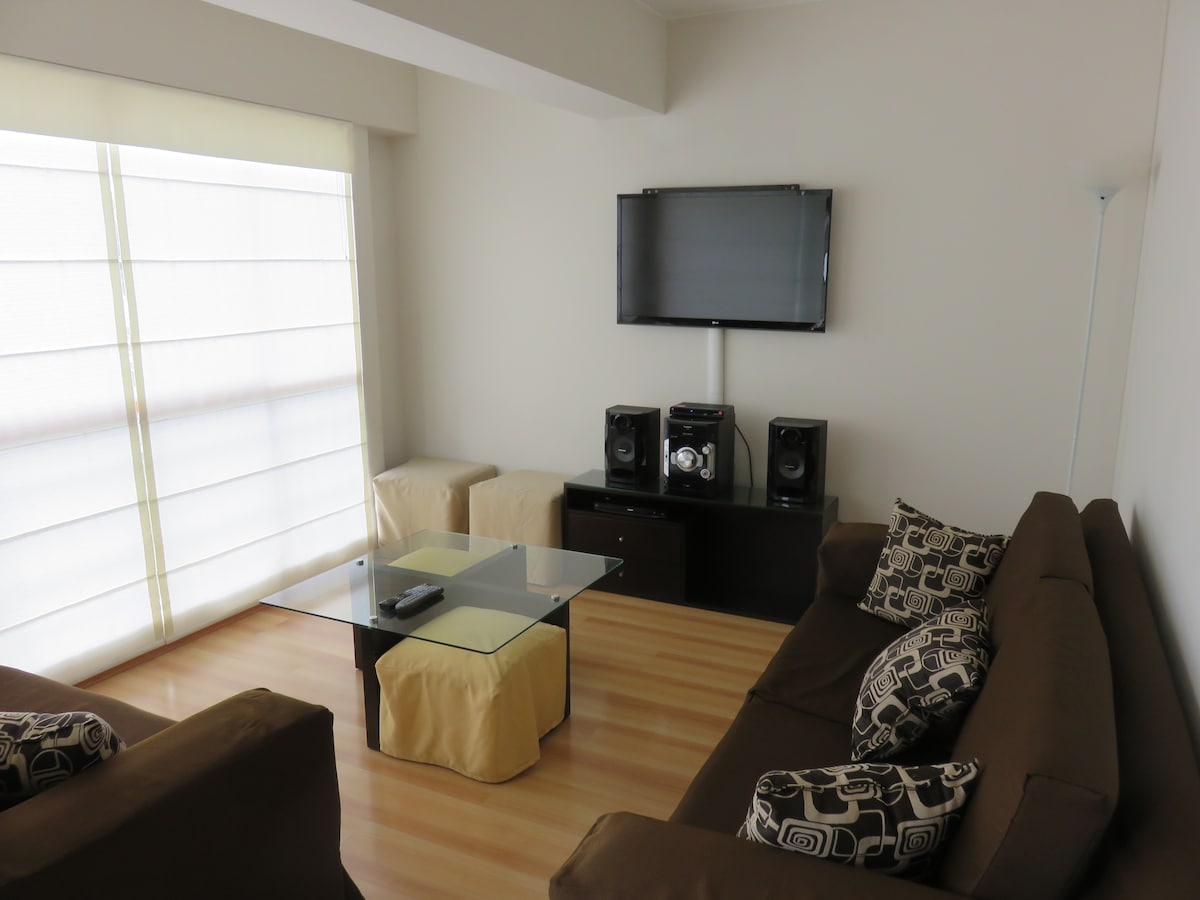 Living room with large wall-mounted LED TV, BluRay DVD, Stereo, HD Cable, Sofas, etc.