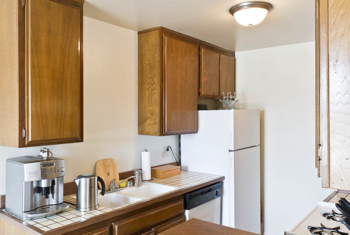 Kitchen with espresso machine, kettle, fridge, stove and dishwasher.