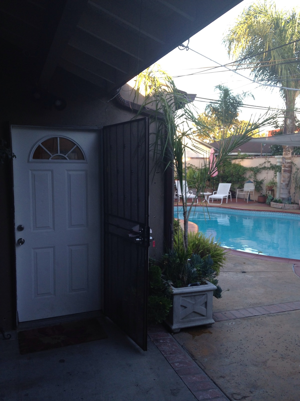 Your front door entrance, with a security screen door for fresh air. And to the right is the pool area.