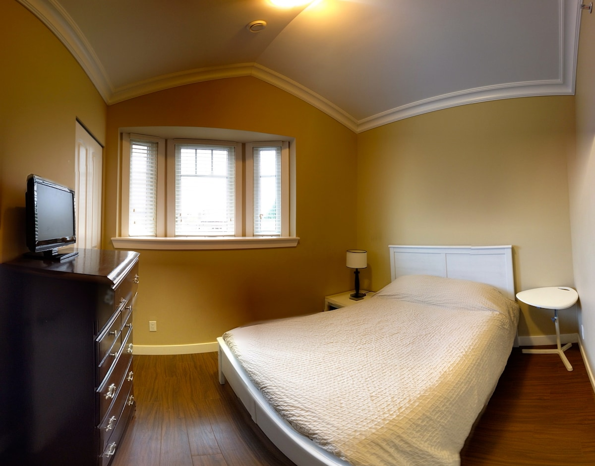 Front bedroom with a double bed, dresser, bay window, and vaulted ceiling.