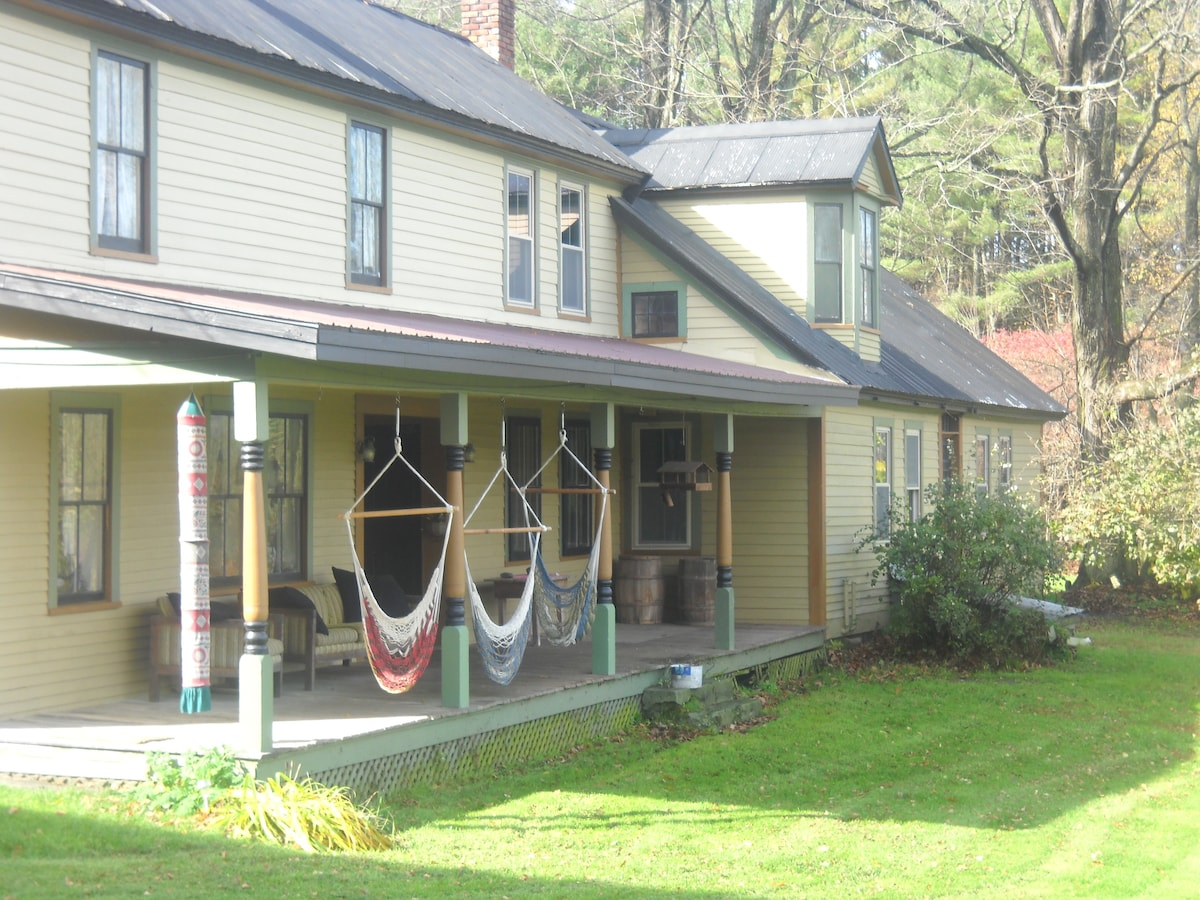 Summer in Vermont with green grass and hammocks on the porch.