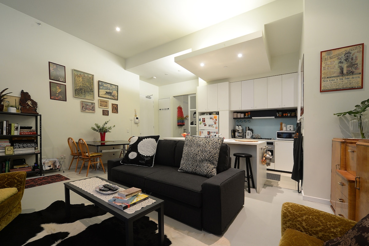 Spacious & inviting living area with three seat sofa, armchairs, scatter cushions, coffee table, TV & fabulous cow hide rug
