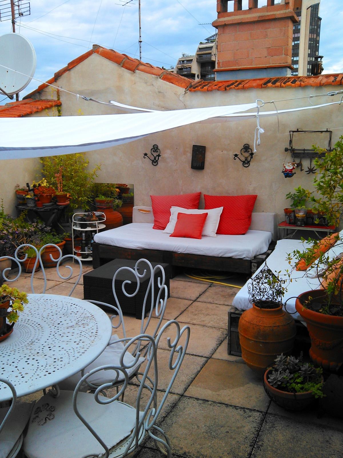 Sur la terrasse , deux canapés , une table et 6 chaises en fer forgé, à l'ombre des voiles suspendues.