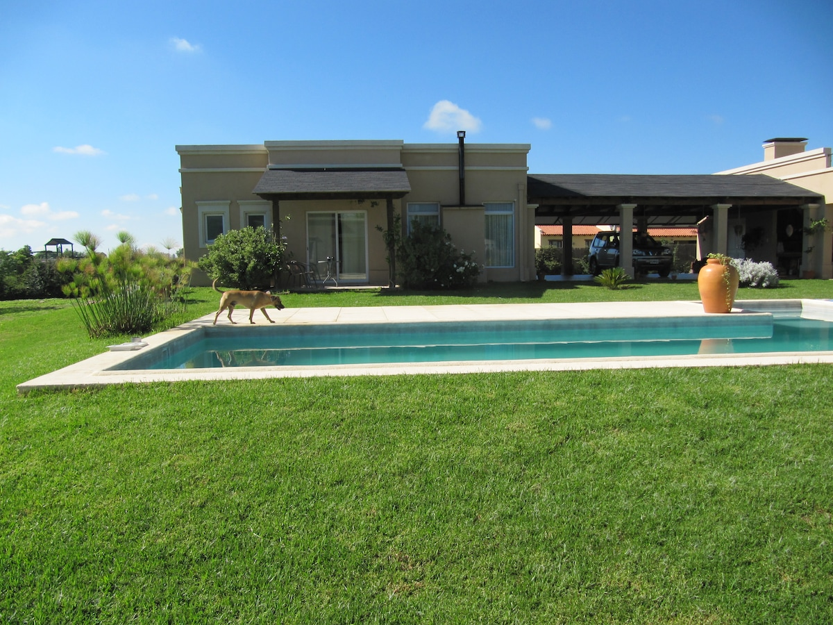 View of the house from the pool side.  This charming independent house  is connected to the main house by a roofed veranda