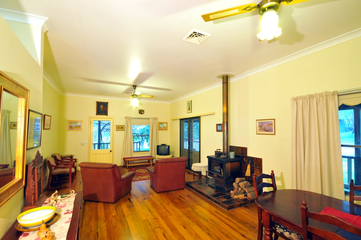 Lounge room and dining area with wood stove, fans and airconditioning