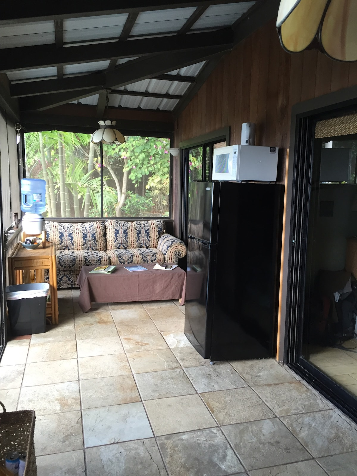Spacious sunroom. Apartment size fridge, microwave, single burner induction cooktop, toaster and hot water kettle. Sofa at the far end of the room is your designated sofa. Perfect for relaxing or an extra guest. NOTE: The fridge and kitchen style amenitie