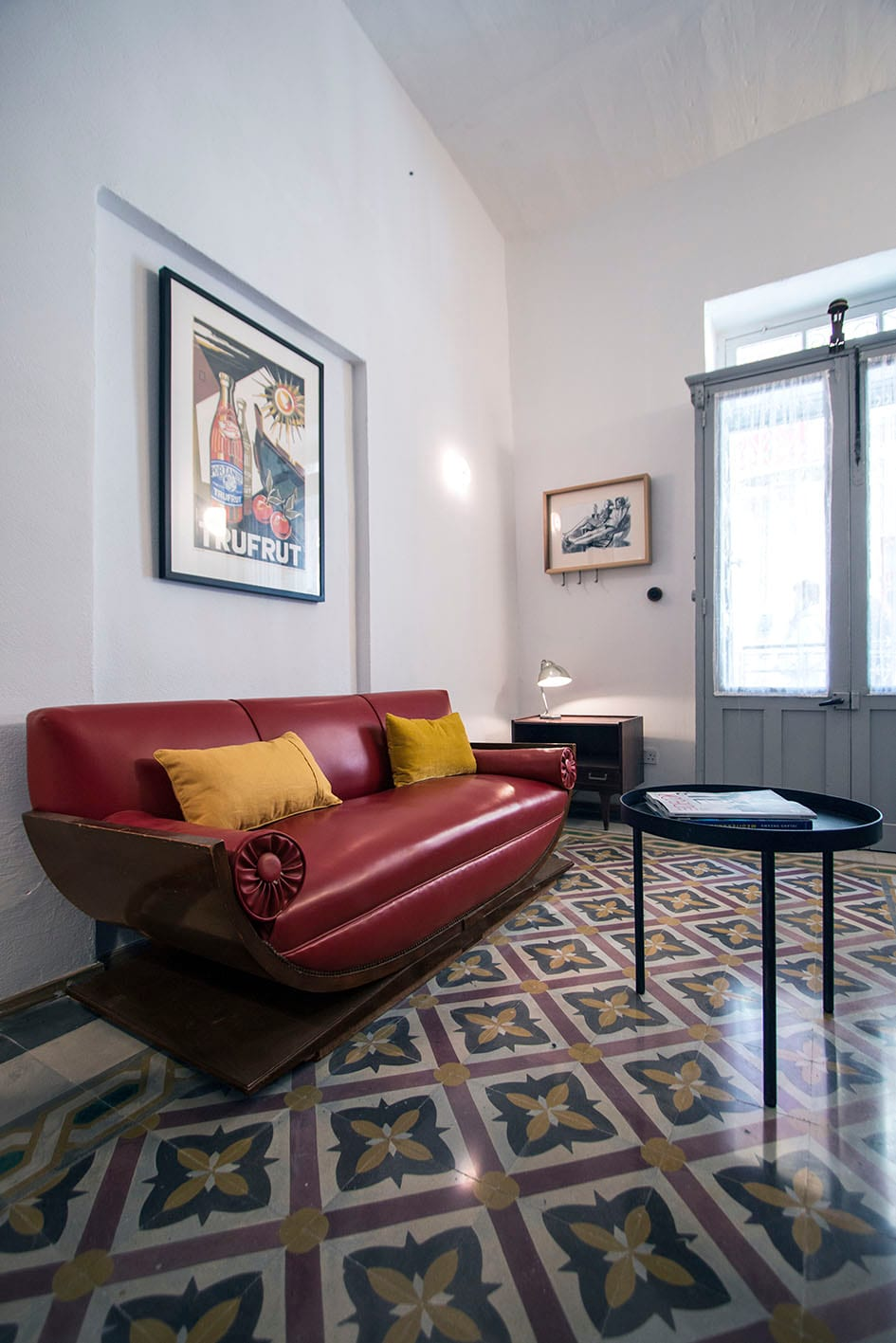 Sitting area upon entry with vintage deco sofa and old, traditional Maltese tiles.