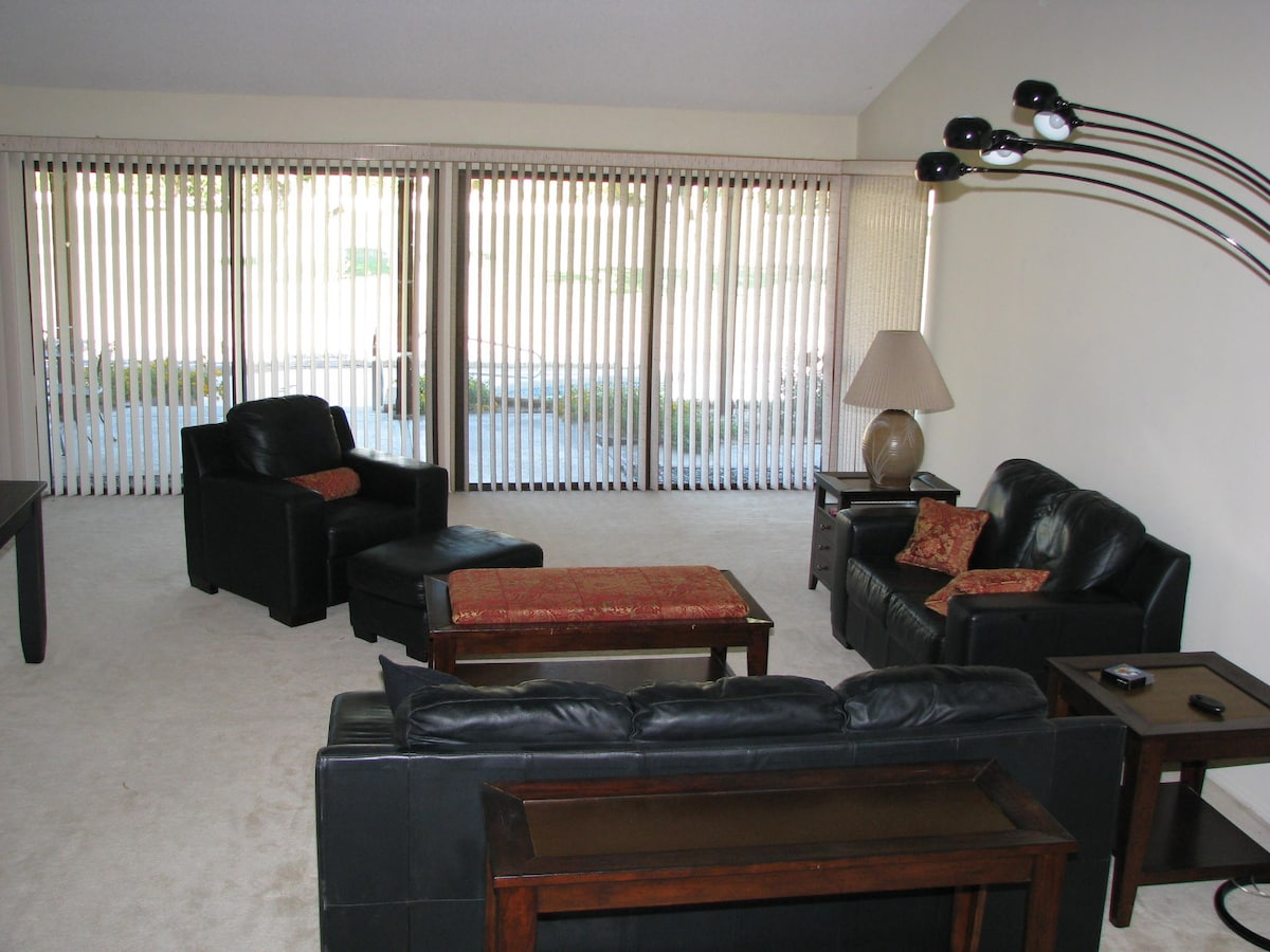Large formal living room with leather furniture, vaulted ceiling and wall of glass overlooking pool area