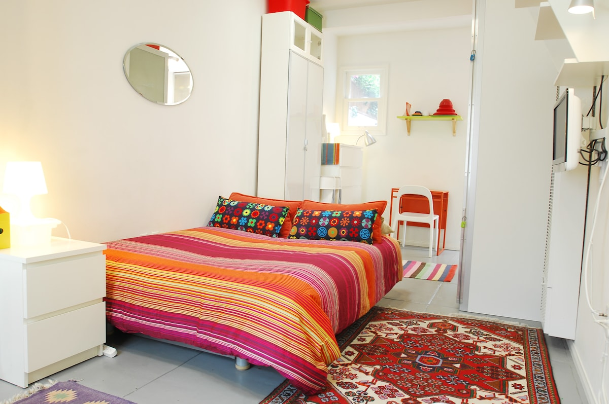 Bed on a bright day (duvet covers vary). Bed is now a 14 inch microfoam mattress. To the rear & right: table, chairs, closet, wall heater  and TV.