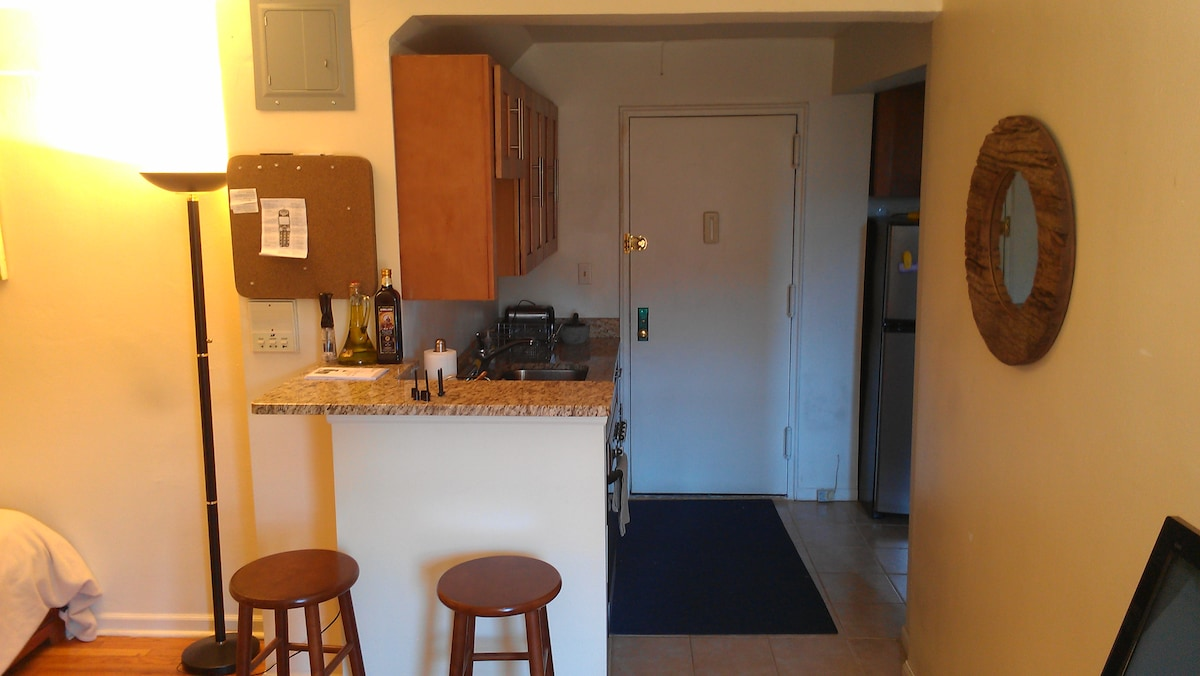 Entry-way with small kitchen and bar stools.