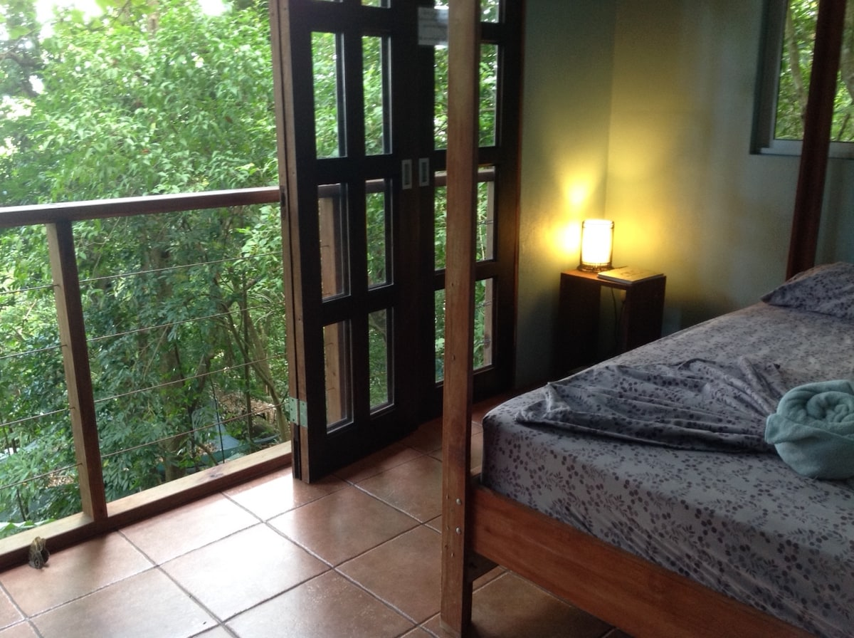 queen bed with view of jungle and ocean