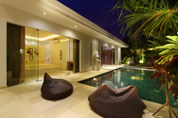 In the line of the pool, find two modern bedrooms behind the glass doors.