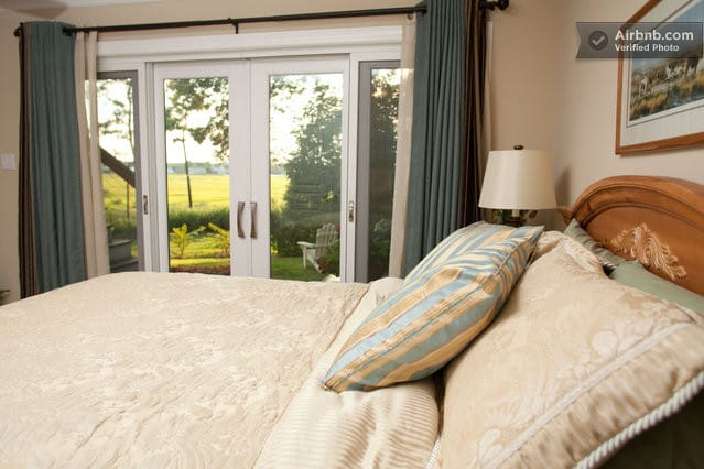 Queen Size Bed overlooking salt marshes with sliders to deck.