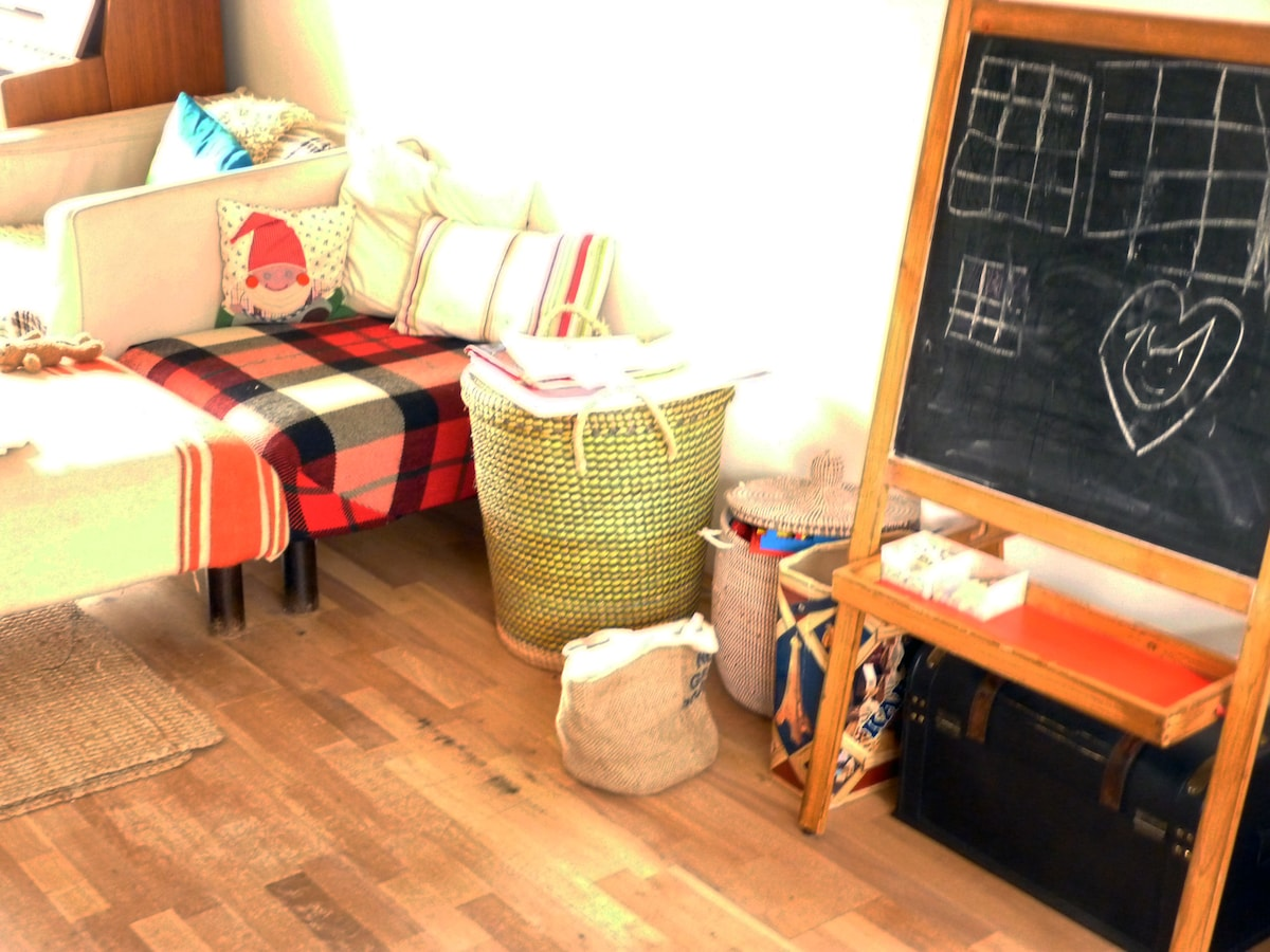 Sitting room, with baskets for children's toys, Lego and Kapla and schoolboard.