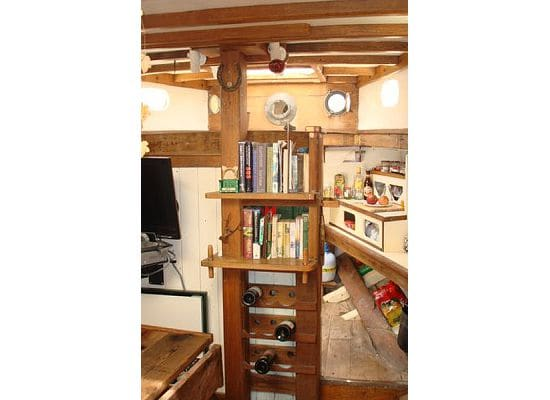 """the """"saloon"""" main living area. the galley is visible behind the bookcase."""