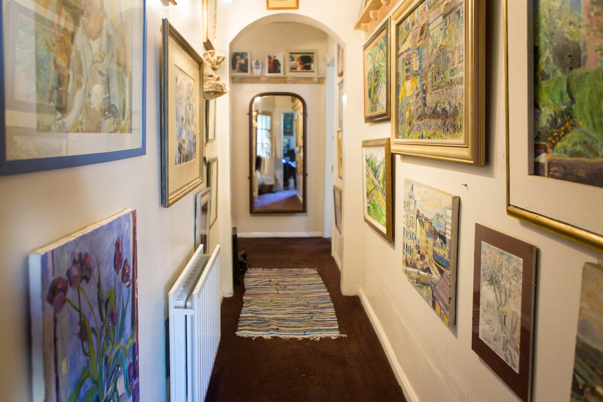 Hallway full of paintings leads to downstairs bathroom and shower.