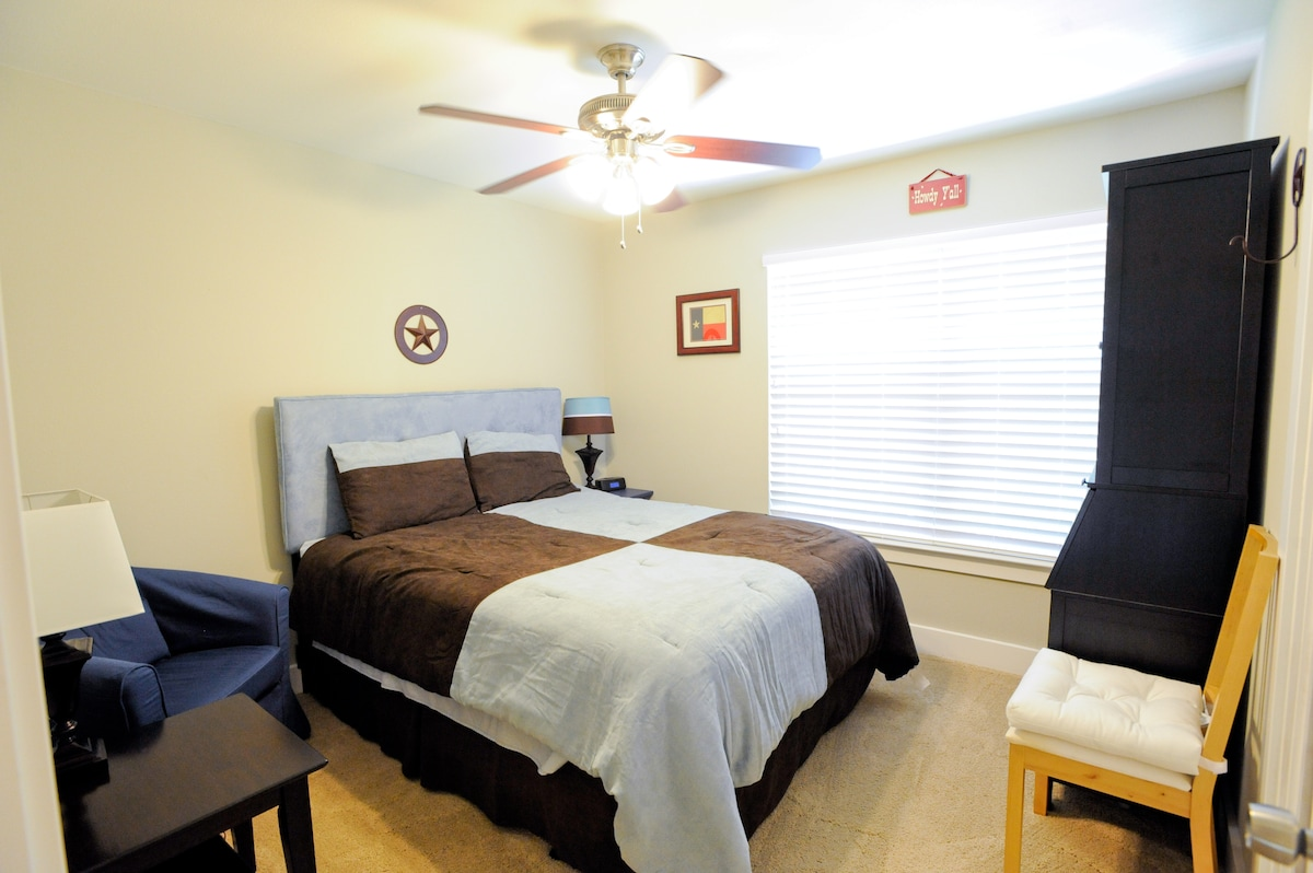 Private guest room with queen size bed, comfortable reading chair, workstation, and private guest closet.