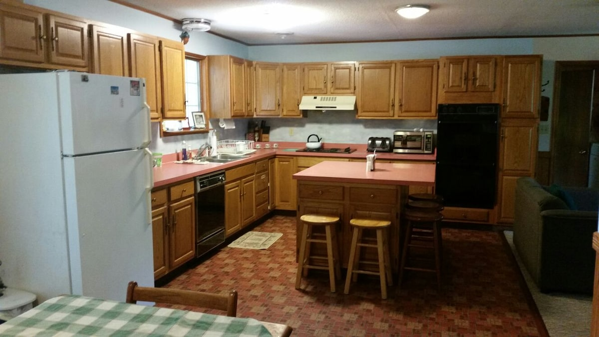 Large kitchen with double oven, stove, fridge, toaster, microwave, dishwasher and coffe maker