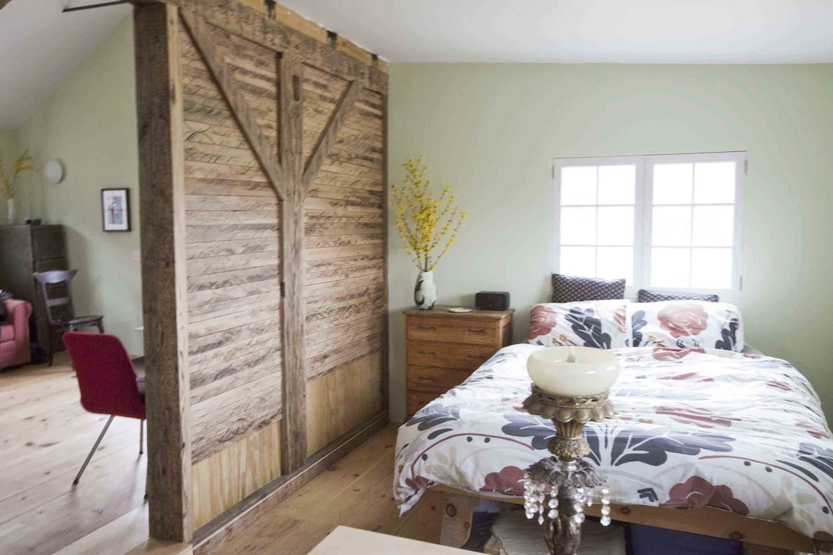 Morning light bounces off the reclaimed wood in the bedroom