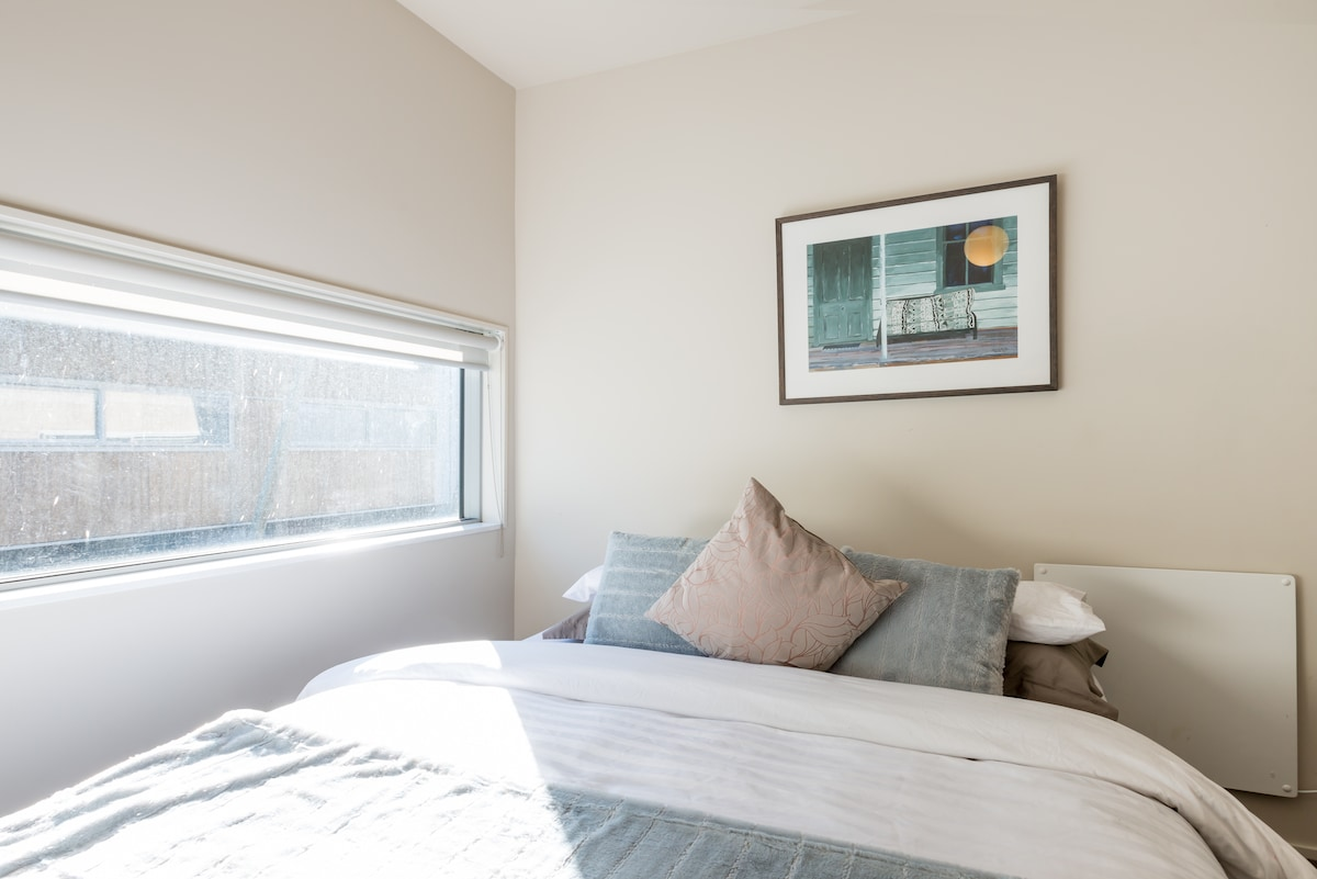 Sun filled warm bedroom with comfortable queen bed