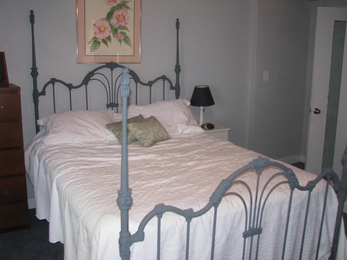 The queen bed in the bedroom.
