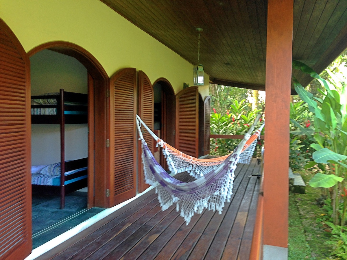 A deck with hammocks in front of the room, with a garden view.