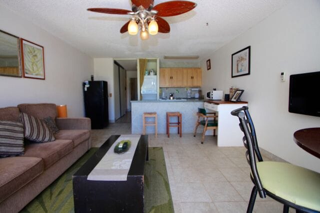 Bright & spacious living room has a pullout Queen size sofabed, ceiling fan, A/C  & bar table for 3.