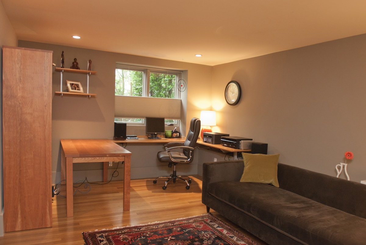 Office with stereo, printer, couch and books galore.