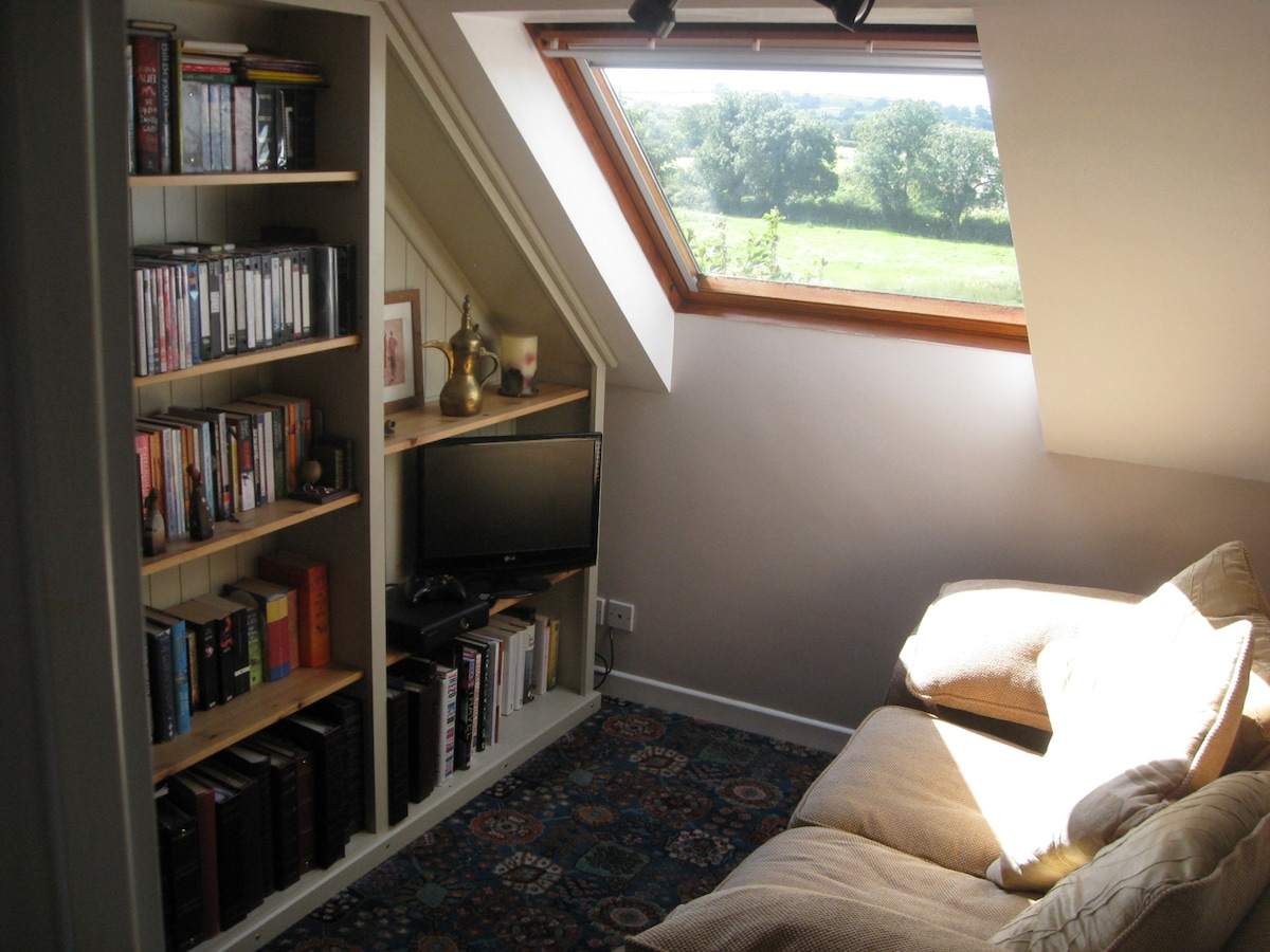 Small lounge area adjacent to bedrooms with TV.