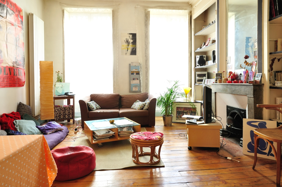 un salon spacieux avec parquet au sol et haut plafond,