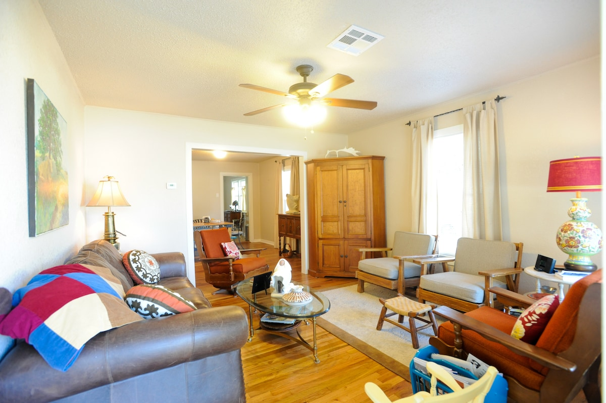 This is the living room with a comfortable leather couch and four chairs for getting together with friends.