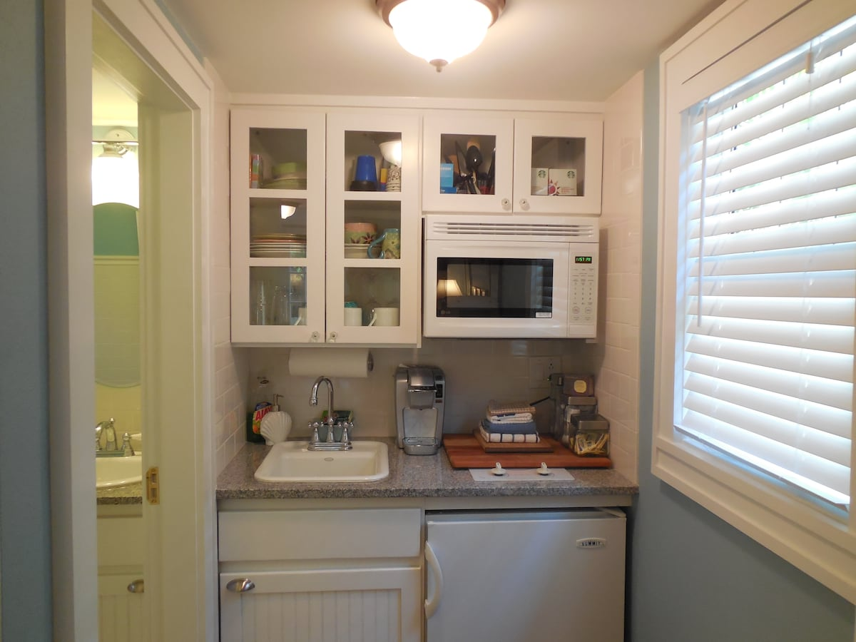 The first floor kitchenette with refrigerator, microwave, sink, coffee maker, blender and toaster.