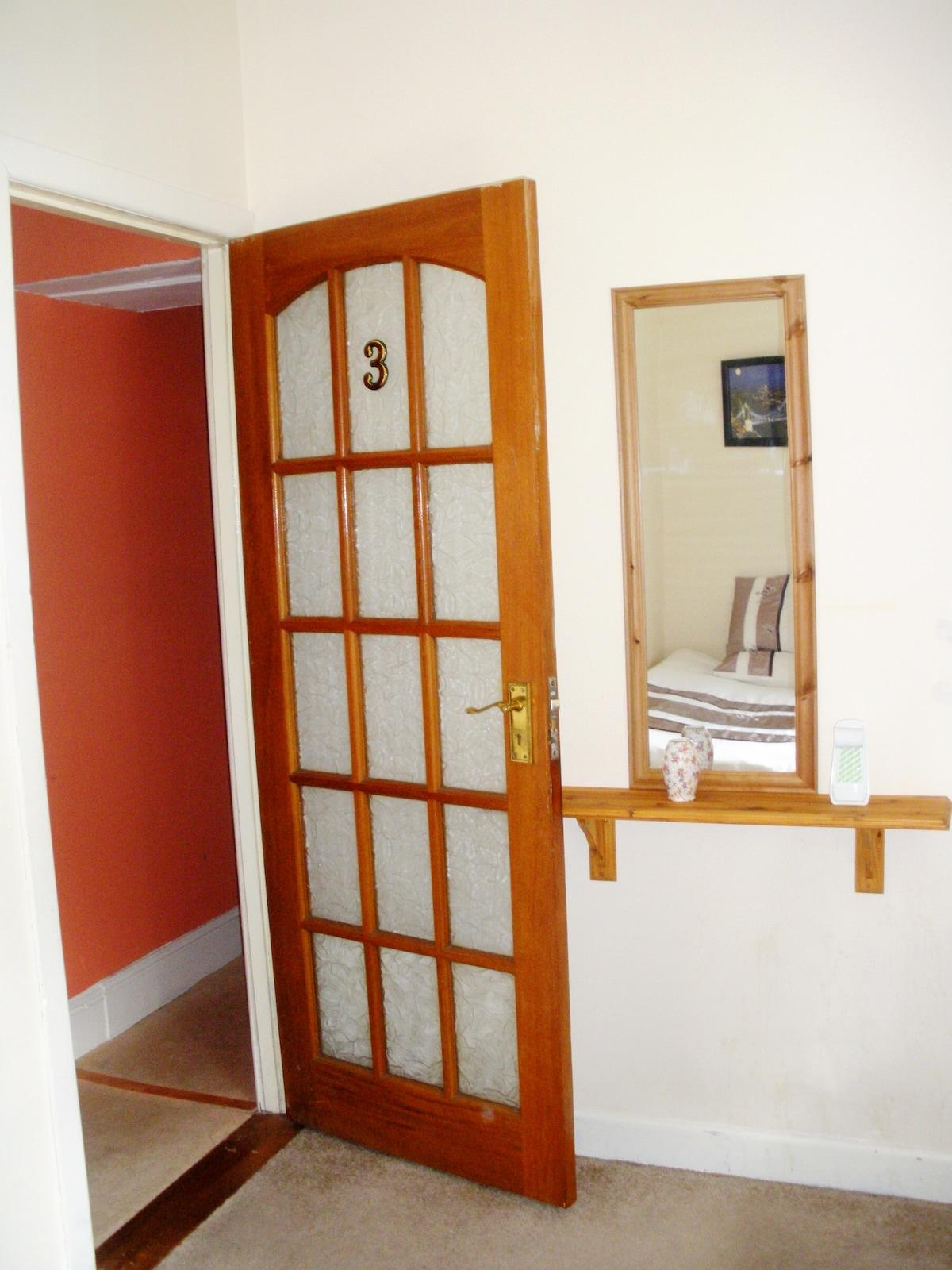 The room's door and hall behind